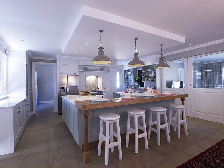 Keith Allan of Stretford Holdings has incorporated design elements that remind one of a country farmhouse kitchen.  The simple lines of the cabinetry and the beautiful old-world light fittings over the seating area hearken back to spaces of yesteryear.  Keith has cleverly included modern design elements and appliances to make this kitchen a luxurious, classic kitchen.  The Ice Snow Caesarstone tops work beautifully with the timber elements included here.