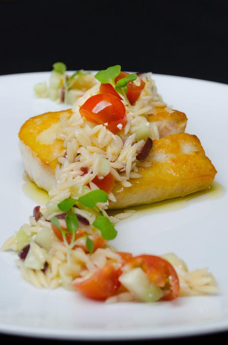pescado blanco fresco, AOEV, limón amarillo, ensalada de risoni con oliva calamata, tomate cherry, brotes de albahaca limón, pepino, queso feta