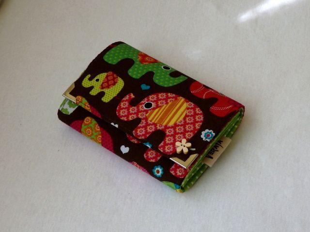 Peněženka se sloníky Peněženka má magnetické zapínání, kapsičku na zip na drobné, přihrádky na doklady a papírové peníze a čtyři kapsičky na karty. Ozdobný přívěšek na zipu a ozdobný dřevěný knoflíček. Ochranné kovové růžky. Rozměry: šířka 13 cm, výška cca 10,5 cm. Peněženku mohu ušít i v jiných rozměrech. Peněženky různých barev a vzorů. Foto ...