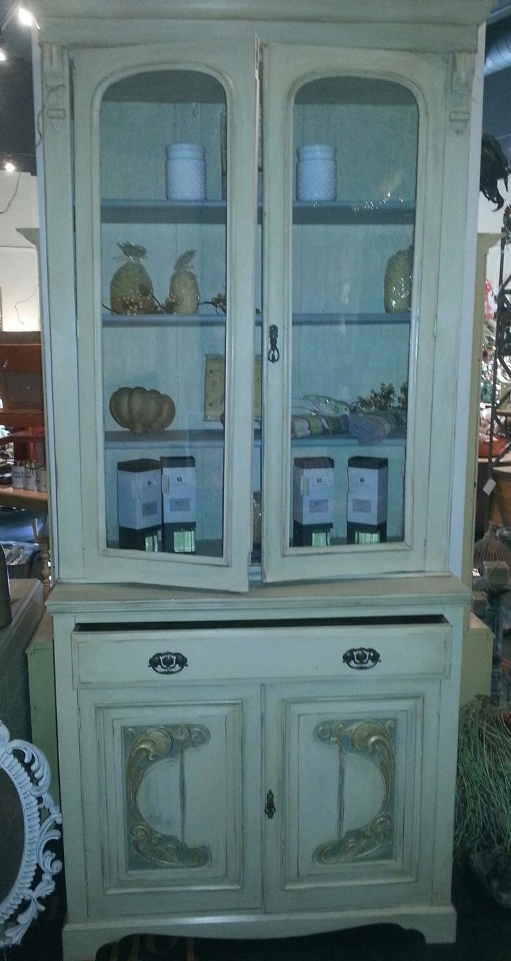 This circa 1900 Art Nouveau china hutch bears the markings of a well used and well loved piece. Refinished using Chalk Paint® by Annie Sloan in Coco and Old White, further enhanced with gold leafing o