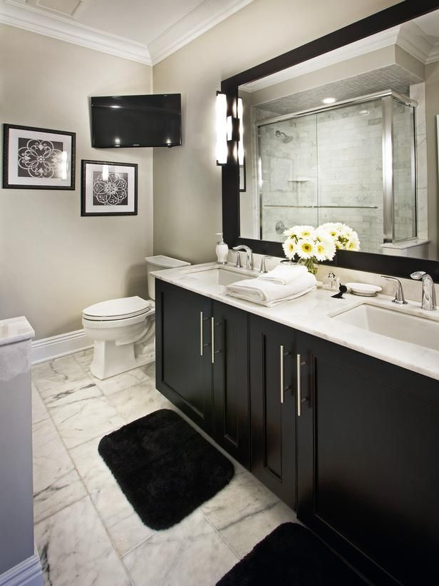 dont miss a beat with this classic black and white bathroom a tv mounted in the corner allows for uninterrupted tv viewing while getting ready in the