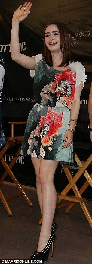 Lily Collins accessorized her floral print Sachin + Babi ensemble with black-and-gold pumps and select bangles.
