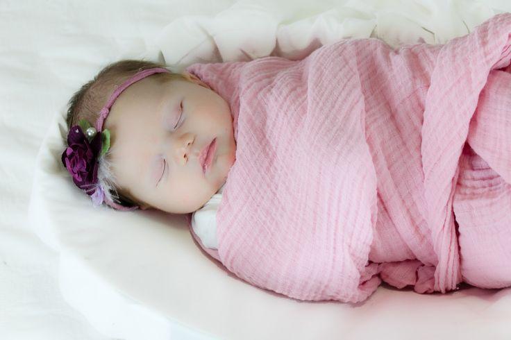 Sleeping sweet swaddled baby with headband