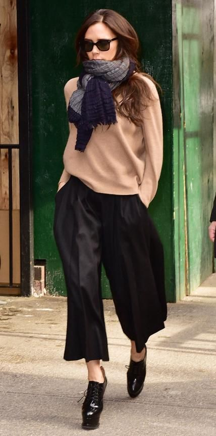 Look of the Day - February 17, 2015 - Victoria Beckham from #InStyle. Even Victoria Beckham's off-duty style is posh! The designer weathered the NYC cold in a cozy camel sweater that she styled with a knotted scarf, sleek black culottes, and platform lace-up heels.