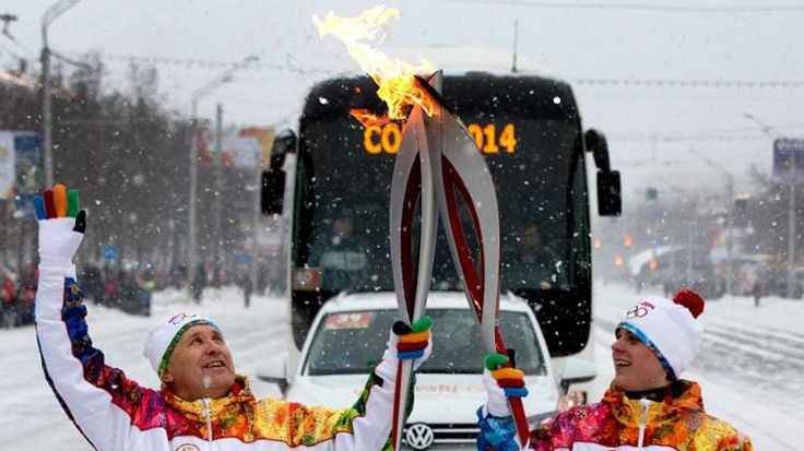Runners 'kiss' with their torches to pass on the Olympic flame in Ufa, regional capital of the Volga River region of Bashkortostan,