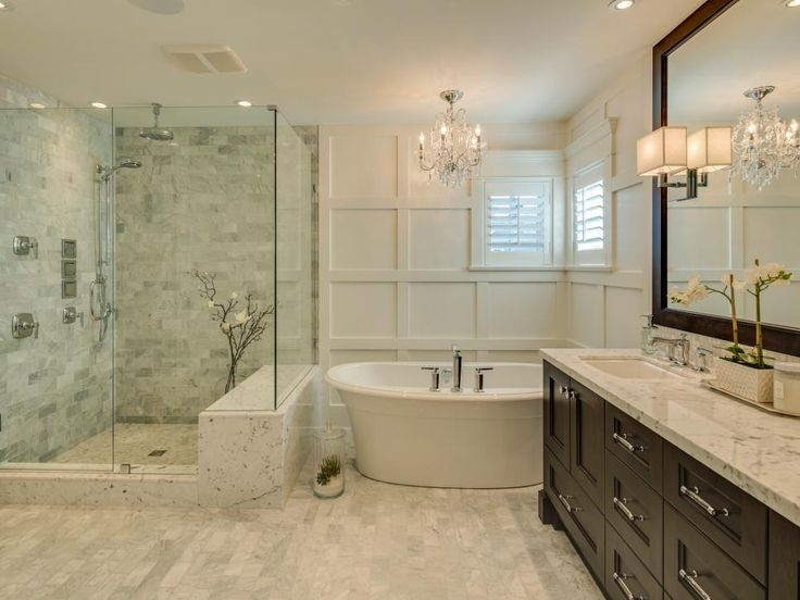 """Bathroom surfaces — flooring, countertops, backsplashes, and walls — can go a long way toward creating an air of elegance. In this luxe master bath, Clay Construction used Italian marble tile inside the shower and on the floor, as well as granite countertops. """"White and neutral tones of gray stone accentuate the darker cabinet finish,"""" says the builder. The finishing touch: """"Wainscoting on the tub-wall gives this bath a truly opulent effect."""""""