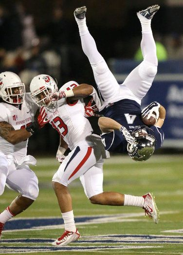 Nevada's Kendall Brock (4) flips through the air after making a reception against Fresno State's Derron Smith (13) and Karl Mickelsen, left, during the first half of an NCAA college football game in Reno, Nev., on Saturday, Nov. 22, 2014. (AP Photo/Cathleen Allison)