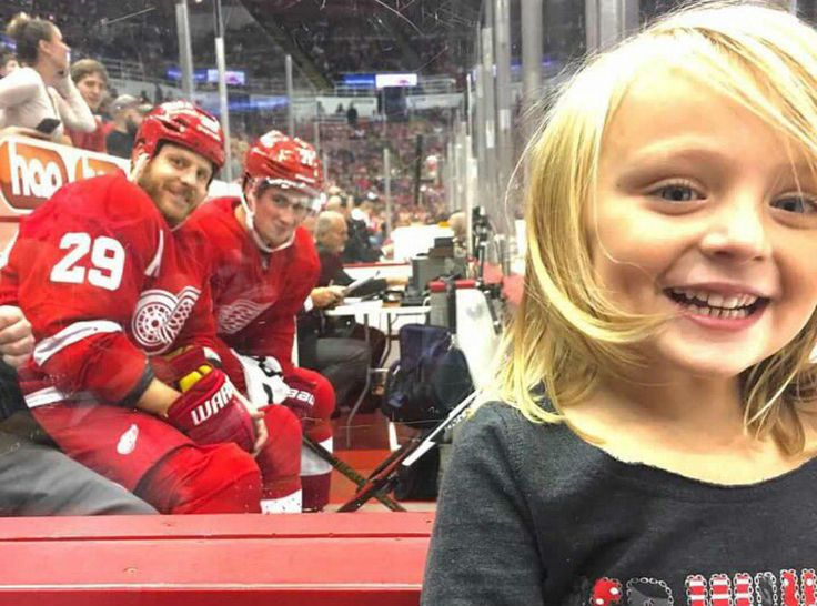 Little Girl photobombed by 2 Red Wings players....