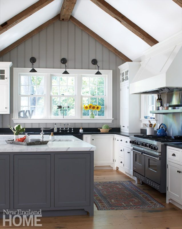 Wood beams and painted beadboard emphasize the vaulting of the kitchen ceiling;  the design team took down walls, allowing the kitchen to flow into the breakfast area and living and dining rooms.