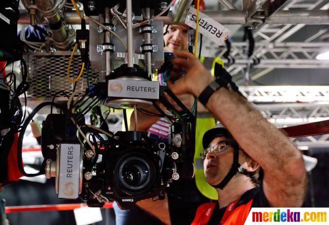 Fotografer Reuters Fabrizio Bensch melakukan pemasangan kamera DSLR di atas kepala robot remote control untuk pertandingan tinju di Olimpiade London.