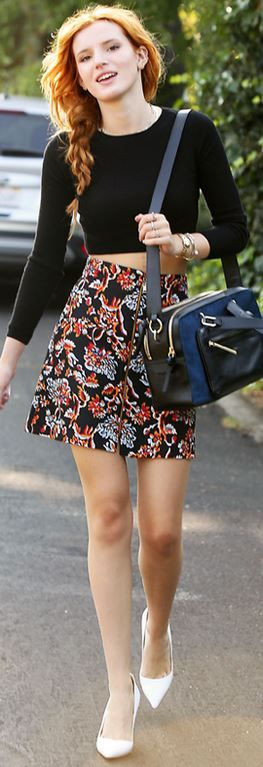 Floral print black skirt, black long sleeve top, black handbag, and white pumps