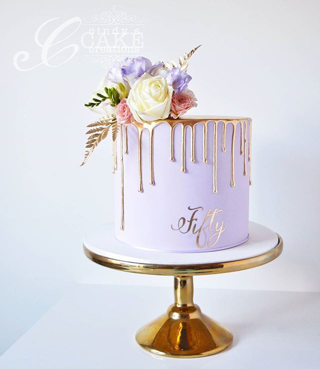 Lavender and dripping gold for a 50th birthday. Cake inside is vanilla with strawberry swiss meringue buttercream.