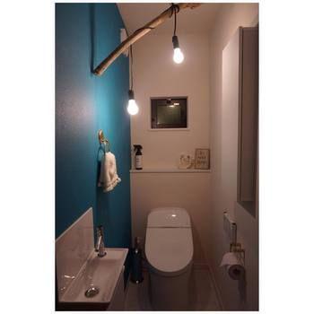 深海にいるような深いブルーの壁が素敵なトイレです。流木を生かした電気の飾り方もとってもおしゃれ。上級者のトイレコーディネートアイディアですね。