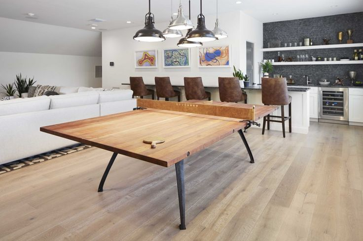 The game room, complete with bar, showcases an industrial-style polished wood and metal ping pong table lit by a makeshift chandelier of warehouse pendants.