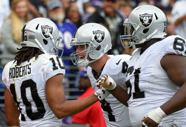 Oakland Raiders wide receiver Seth Roberts, left, celebrates his touchdown with quarterback Derek Carr, center, and center Rodney Hudson in the first half of an NFL football game against the Baltimore Ravens, Sunday, Oct. 2, 2016, in Baltimore. (AP Photo/Nick Wass)