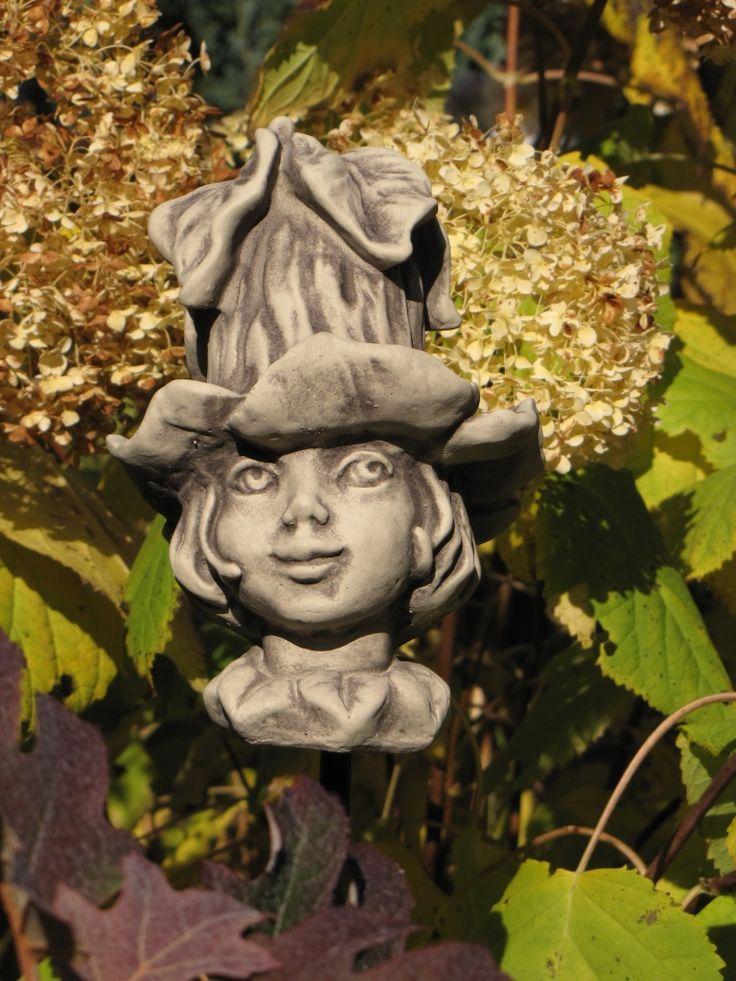 Blumenkind Glockenrebe aus Betonguss  Das Blumenkind Glockenrebe, dessen Kopfbedeckung den Blüten der Glockenrebe (Cobaea scandens) nachempfunden ist, verschönern jeden Garten und zaubern ein Lächeln in Ihr Gesicht.  Verschmitzt lächelnd oder mit einem verträumten Gesichtsausdruck verbreiten die Blumenkinder eine romantisch-verspielte Atmosphäre. Mit nur einem Blick schließt man die kleinen Dekofiguren ins Herz.