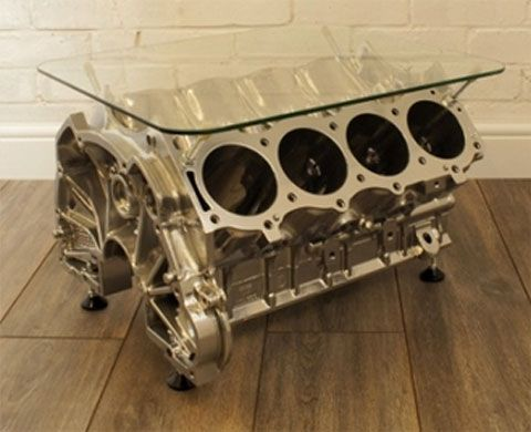 An original salvaged Rover V8 engine block professionally powder coated in a gleaming chrome finish - sitting on self levelling height adjustable feet with an 8mm thick made to measure piece of polished and toughened safety glass.