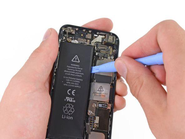 6. Bruk et plaståpningsverktøy langs batteriets høyre kant og lirk på flere punkter slik at du skiller det fra limet som fester det til bakdekselet.