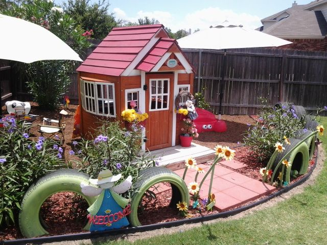 Backyard children's play area.  Recycled tires for fence, whimsical flowers, umbrellas for shade over sand box and tables.