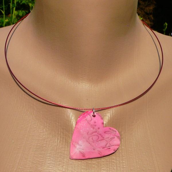 Collier en forme de cœur, réalisé en pâte fimo de couleur rose, avec fausses écritures texturée. Le collier est en fil câblé rose, et reste parfaitement en forme de par son épaisseur.  En vente ici : http://www.operlines.fr/products-page/collier/collier-fantaisie-fimo-rose/