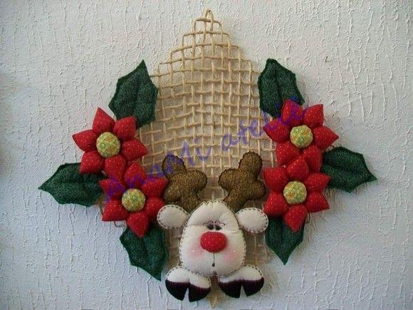 Guirlanda de porta Rena com flores em feltro e tecido costurado à mão, com suporte em palha.