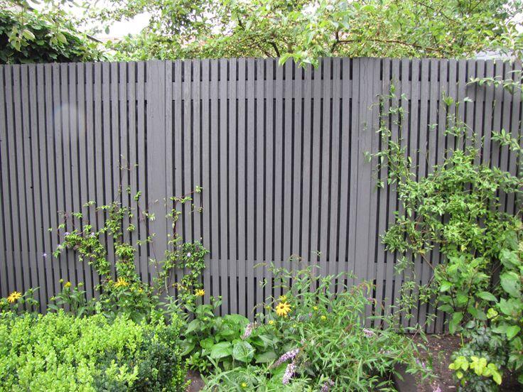 een latwerk schutting op de grens en een 'opbergladebankje'in een tuin te Amstelveen