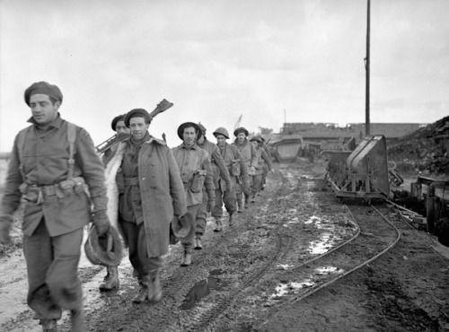 Infantrymen of Le Régiment de la Chaudière marching along a dike near Nijmegen, Netherlands, 10 February 1945. McDougall, Colin Campbell., Photographer