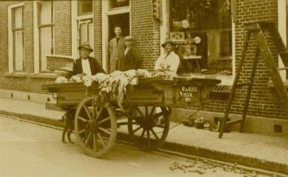 Willem de Boer met zijn hondenkar voor de bakkerij van Sjouke v.d. Veer aan de Hoofdstraat in Koudum. Foto tussen 1920 en 1940.