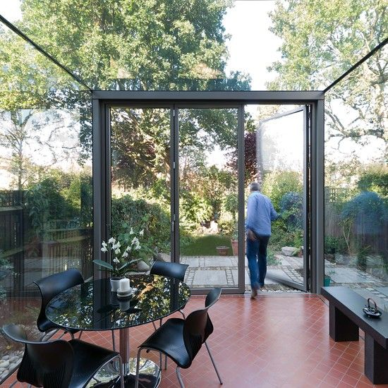 This ultra-modern conservatory creates a seamless to the outdoors thanks to the vast expanse of glass