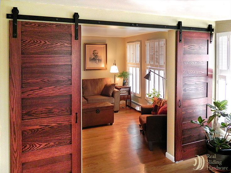 This is what I want to do in my living room before I sell my house someday.  Only make the doors myself from some (hopefully!) beat-up wood, and build to look like a real barn door.  Vertical boards, rustic framing on the top and bottom.  ;-)  If only the hardware weren't SO flippin expensive!!!  (like $800 a track)