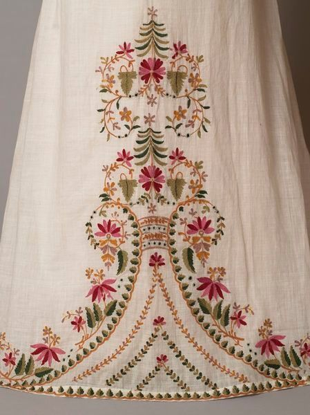 1812-1815 - England - Girl's dress of white muslin embroidered from the hem with a floral design in coloured wools. The dress has a high-waisted bodice, vertically-gathered puffed sleeves and a trained skirt. Muslin embroidered in wool (V Museum) by britney