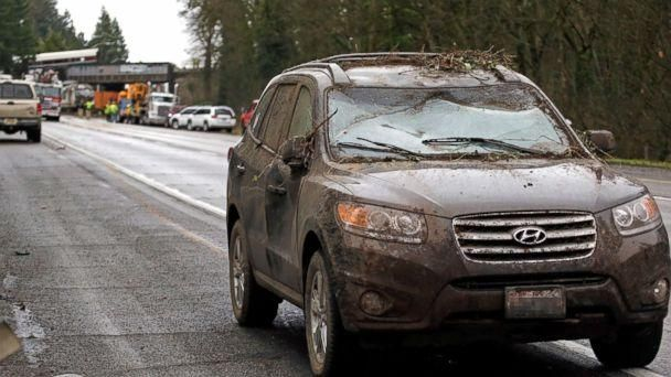 PHOTO: A car covered in mud and debris with a smashed windshield and other damage sits parked on the shoulder just beyond where an Amtrak train derailed onto Interstate 5, Dec. 18, 2017, in DuPont, Wash. (Elaine Thompson/AP)