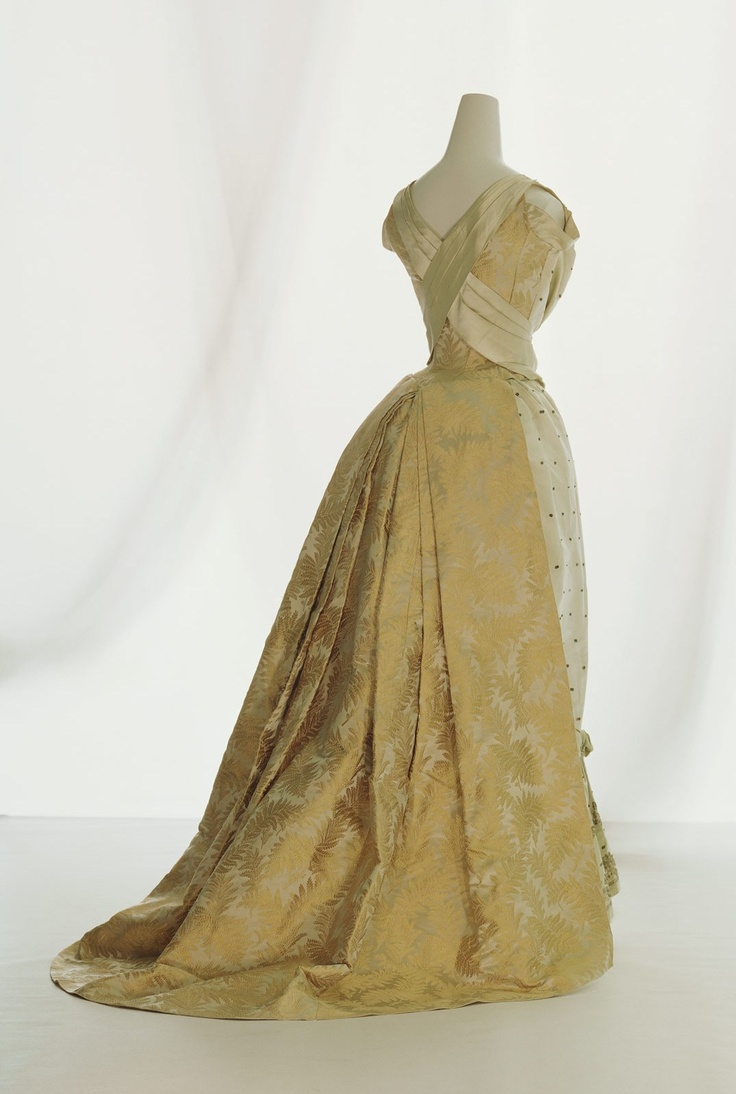 """Ball Gown, Rouff, Paris, France: ca. 1888, embroidered silk satin with metallic threads and sequins, silk brocade train. """"In the second half of the 19th century, Lyon silk manufactures who produced the materials used in Paris """"Haute Couture"""" kept their eyes to the popular Japonism trend as a new design source.  In the latter half of the 1880s the bustle reduced in size, and the entire dress changed to a more simple style. At the rear of the skirt, vestiges of the bustle style remained..."""""""