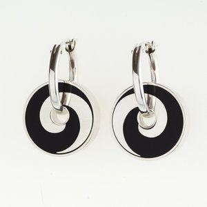 Black Swirl Pinwheel Earrings by Victoria Varga. Reversible pinwheel earrings hang from a hinged silver hoop. These earrings are hand fabricated using a unique layering process combining resin, powdered pigments and mica. The backs are purple.
