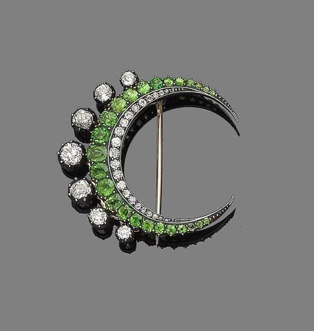 A garnet and diamond crescent brooch, last quarter of the 19th century. The graduated rows of old brilliant-cut diamonds and oval-cut demantoid garnets, highlighted by similarly-cut diamonds in pinched collet-settings, mounted in silver and gold