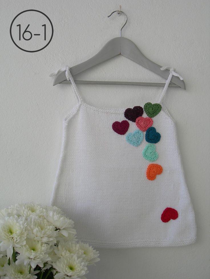 Vestido en punto jersey y color blanco. Aplicaciones de corazones de colores y tirantes para atar en ganchillo.