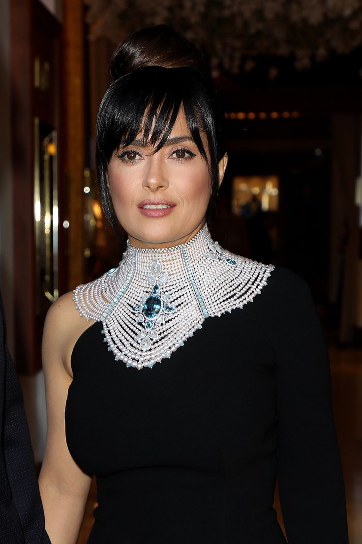 Salma Hayek wore a show stopping Boucheron high jewellery Baïkal necklace high neck collar set with a 78.33 carat Santa Mariaoval aquamarine, moonstones and Akoya cultured pearls, paved with diamonds and aquamarines, on white gold. With a black dress and high bun. For glamour celebrity fashion Cannes Film Festival red carpet jewellery spotting travel here: http://www.thejewelleryeditor.com/jewellery/top-5/best-red-carpet-jewellery-jewelry-cannes-film-festival-2017-weekend/ #jewelry