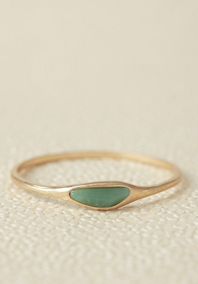 A milky jade green stone ornaments this gold-toned bangle for a simple, luxurious look.