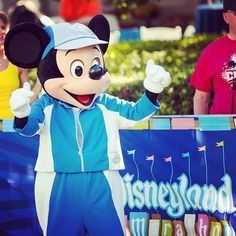 Mickey in his athletic outfit cheering on runners in the Disneyland Marathon