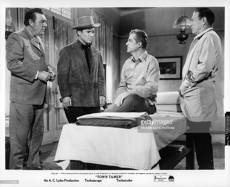 "Lon Chaney Jr and Richard Jaeckel look at a sitting Dana Andrews as Richard Arlen watches on in a scene from the film ""The Town Tamer,"" 1965."