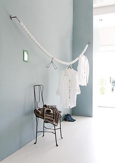 clothes line indoors or out ... what a great way to prevent the hangers from sliding around ... string hollow plastic balls, ping pong balls, wiffle balls, etc on the line and place hangers in between the balls. Also makes an interesting graphic element out of a simple clothes line!
