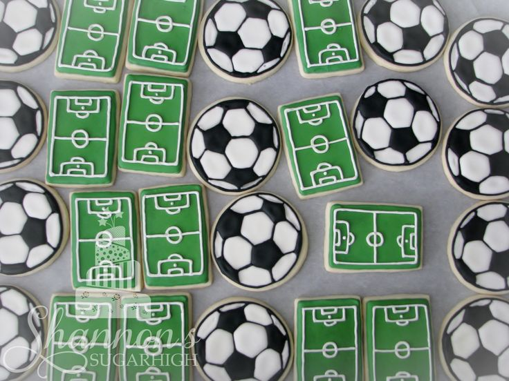 Soccer balls and soccer fields royal icing painted shortbread cookies in white, black, and green. Keyword: Sugar cookie.