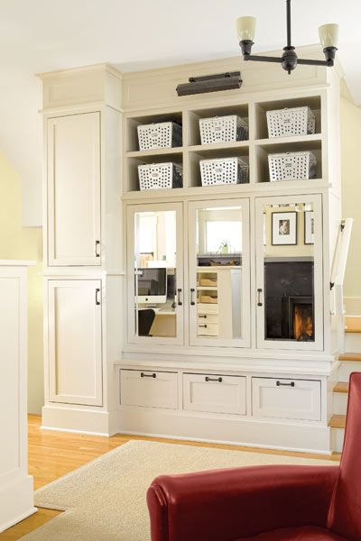 Beveled-mirror fronts add a formal note to this stair-wrapped built-in that serves as a coat closet. Stacked cabinets at one end hold hooks for kids' outerwear below and a charging station and files above. | Photo: Alex Hayden | thisoldhouse.com