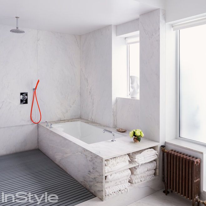 White kitchen with marble backsplash, and an open shower