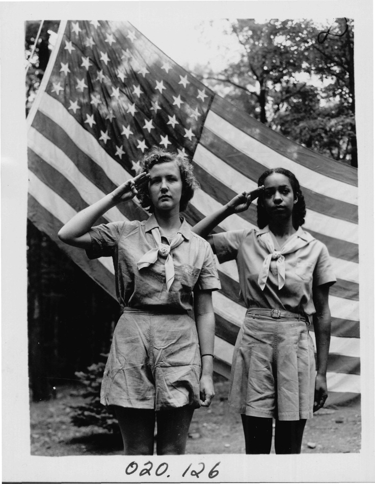 Girl Scout Seniors salute the American flag at camp circa 1940s.