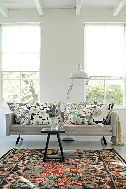 colorful patterned rug and cushions on a luminous neutral background