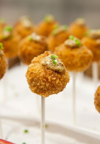Five Cheese Mac-and-Cheese Lollipops composed of elbow macaroni and Gruyère, pecorino, Parmesan, white cheddar, and fontina cheeses, the hors d'oeuvre is coated in panko and served alongside a tangy mustard sauce