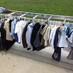 Great idea for displaying clothes at a garage sale! Turn a ladder horizontally and lay each side on a table and hang clothes from both sides!