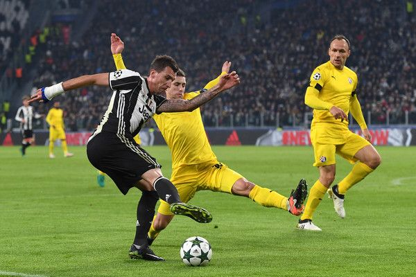 Mario Mandzukic (L) of Juventus is challenged by Josip Pivaric of GNK Dinamo Zagreb during the UEFA Champions League Group H match between Juventus and GNK Dinamo Zagreb at Juventus Stadium on December 7, 2016 in Turin.