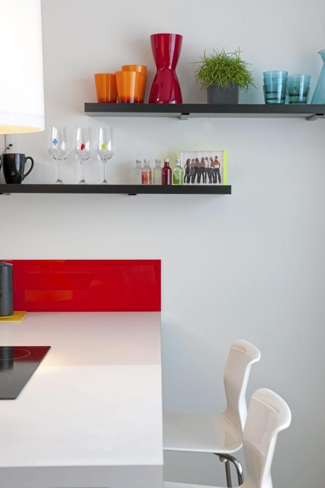 Beboeren har brukt nøytrale farger som base og spedd på med dristige farger i detaljene. Ved å ha åpne hyller i stedet for overskap får serviset en estetisk funksjon i tillegg til den praktiske.